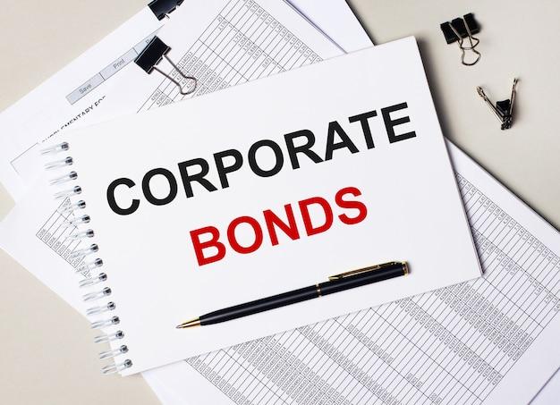 Auf dem desktop liegen dokumente, stift, schwarze büroklammern und ein notizbuch mit dem text corporate bonds. unternehmenskonzept