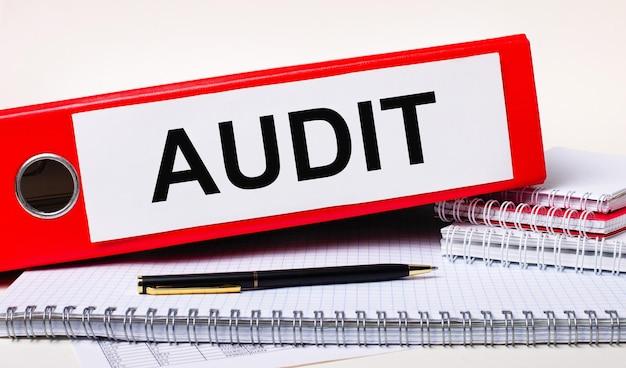 Auf dem desktop liegen notizbücher, ein stift und ein roter ordner für papiere mit dem text audit. geschäftskonzept