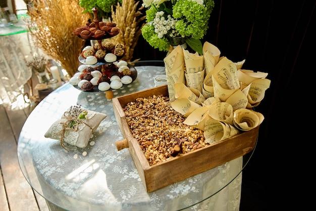 Auf dem festlichen tisch werden hochzeitssüßigkeiten, dekorationen aus holz und wildblumen serviert