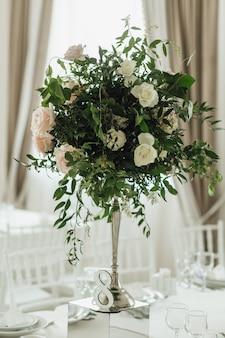 Auf dem festtisch steht ein grüner strauß mit rosen