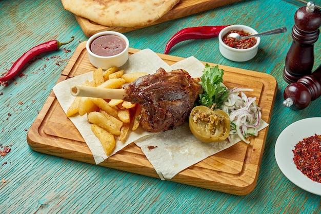 Auf dem feuer gegrillte lammkeule mit roter sauce und kartoffeln auf einem grünen tisch. östliche küche