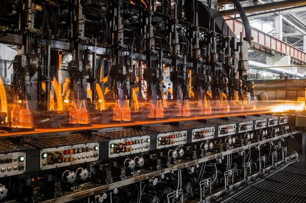 Auf dem förderband werden glasflaschen pasteurisiert mit feuerproduktion von glasflaschen und getränken