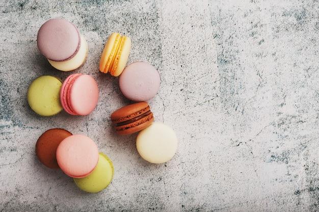 Auf dem grauen tisch liegen französische makkaroni-kekse in verschiedenen farben. stillleben von süßwaren.