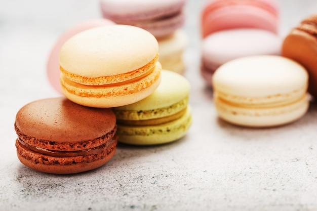 Auf dem grauen tisch stehen französische macaron-kekse in verschiedenen farben