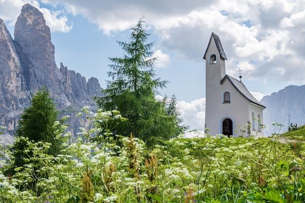 Auf dem grödner joch befindet sich diese kleine weiße kirche mit blick auf die sellagruppe im herzen der dolomiten