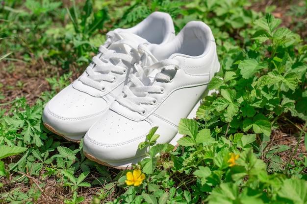 Auf dem grünen gras stehen weiße damenturnschuhe. modische bequeme schuhe für den sport.