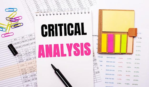 Auf dem hintergrund der grafiken liegt ein notizbuch mit den worten kritische analyse, ein marker, farbige büroklammern und helles notizpapier