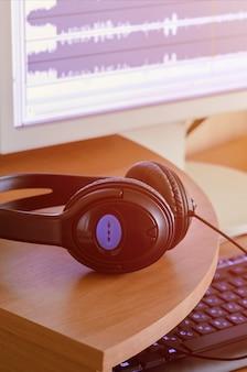 Auf dem hölzernen desktop des sounddesigners liegen große schwarze kopfhörer