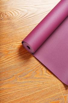 Auf dem holzboden ist eine lila yogamatte gedreht. gesunder lebensstil, sport