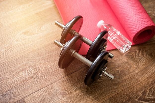 Auf dem holzboden liegen eine rosa sportmatte, eine flasche sauberes wasser und zwei zerlegte hanteln. heimtraining.