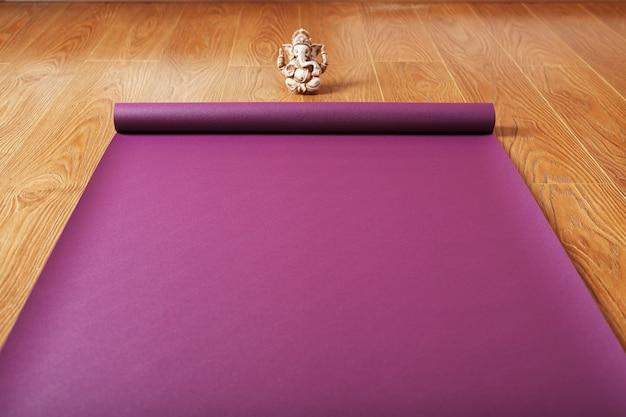 Auf dem holzboden liegt eine fliederfarbene yogamatte mit einer ganapati-figur ausgebreitet