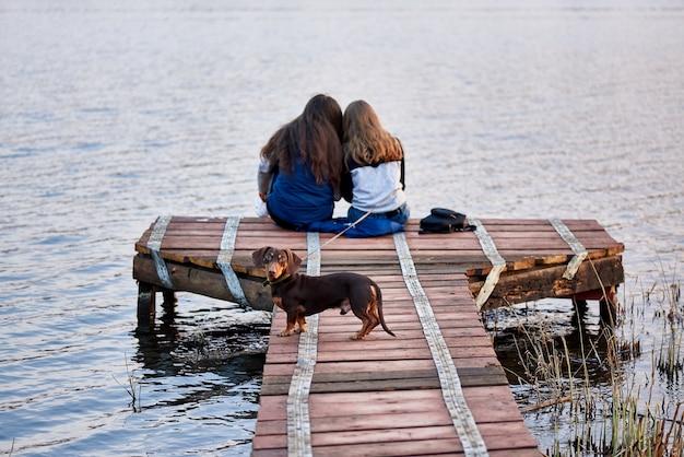 Auf dem holzsteg am see stehen zwei junge frauen mit einem hund.