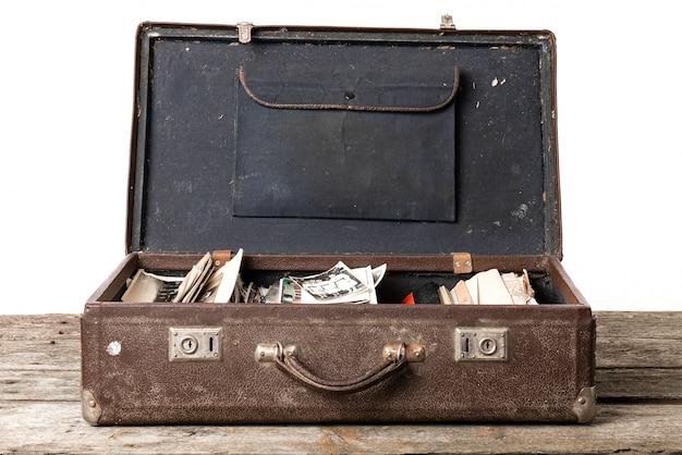 Auf dem holztisch steht ein offener brauner vintage-koffer mit schwarzweißfotos
