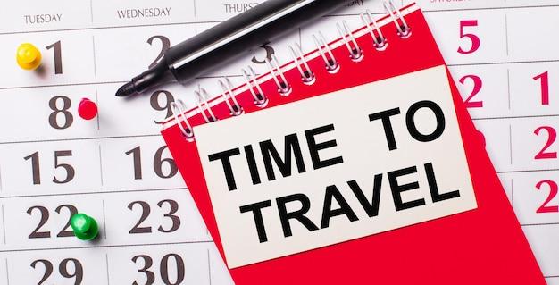 Auf dem kalender befindet sich eine weiße karte mit dem text time to travel. in der nähe befindet sich ein roter notizblock und ein marker. sicht von oben