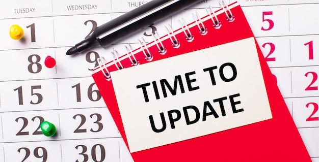 Auf dem kalender befindet sich eine weiße karte mit dem text time to update Premium Fotos