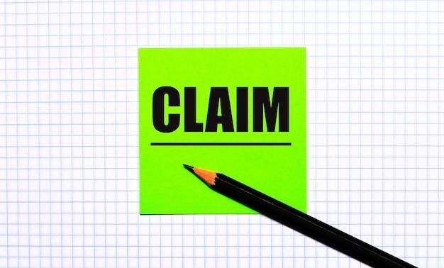 Auf dem karierten papier befindet sich ein grüner aufkleber mit dem text claim und ein schwarzer stift.