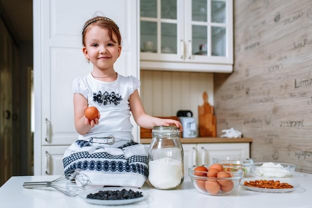 Auf dem küchentisch sitzt ein lächelndes kleines mädchen mit einem ei in der hand