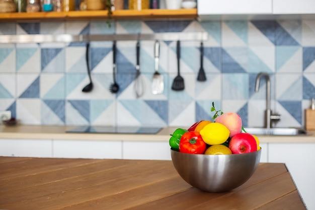 Auf dem küchentisch steht eine große schüssel mit obst und gemüse, der hintergrund verschwimmt