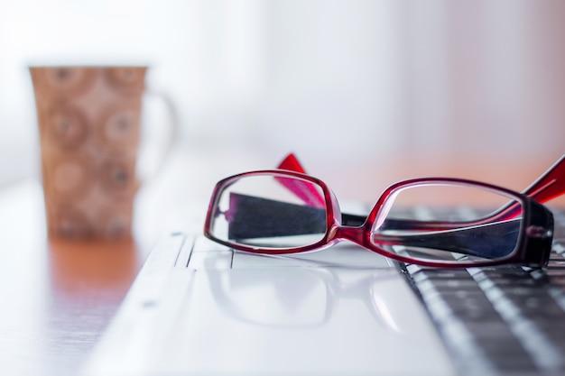 Auf dem laptop liegen brillen, weiter auf dem tisch steht eine tasse, in der büropause