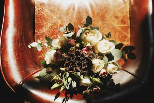 Auf dem lederstuhl steht ein origineller brautstrauß aus weißen rosen und trockenen blumen