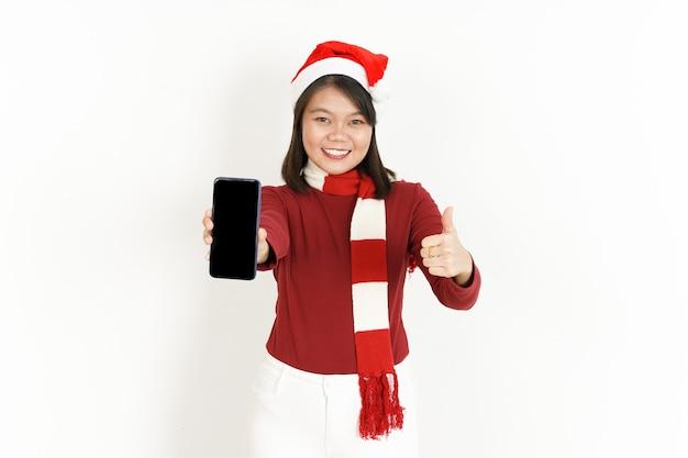 Auf dem leeren bildschirm des smartphones und dem daumen nach oben einer asiatischen frau mit rotem rollkragen und weihnachtsmütze angezeigt