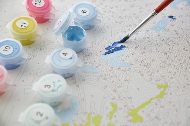 Auf dem leinwandhintergrund liegen nummerierte behälter mit farben und pinseln. kreative freizeitaktivitäten