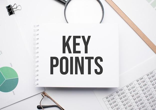Auf dem notizblock zum schreiben des textes key points, lupe, diagramme und brille.