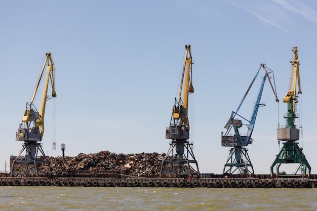 Auf dem pier liegt ein großer haufen metallschrott, der mit hilfe von kränen in das schiff geladen werden soll