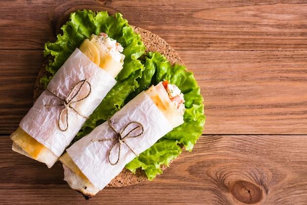 Auf dem salat lagen zwei mit käse, huhn und tomaten gefüllte pita-brötchen. ansicht von oben