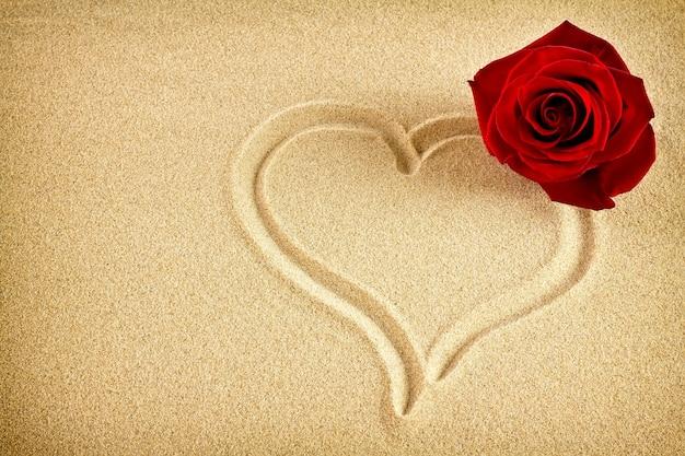 Auf dem sand auf das herz gezeichnet und rote rose.