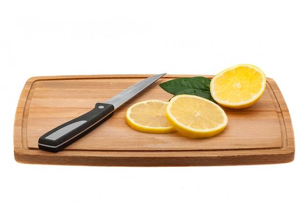 Auf dem schneidebrett sind ein paar frische zitronenscheiben, ein küchenmesser und grüne blätter