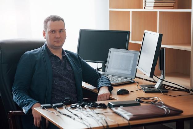 Auf dem schwarzen stuhl sitzen. der polygraph-prüfer arbeitet im büro mit der ausrüstung seines lügendetektors