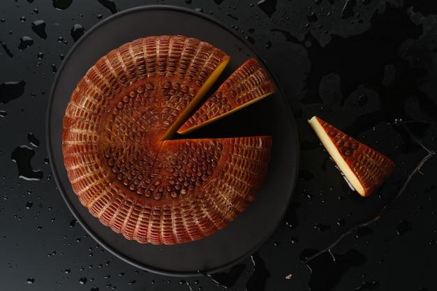 Auf dem schwarzen tisch geschnittener geräucherter käse