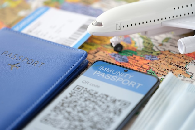 Auf dem smartphone-bildschirm immunitätszertifikat gegen covid-flugticket und reisepass auf dem tisch