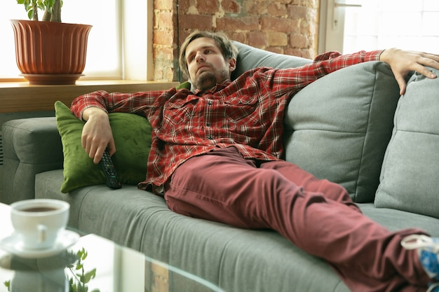 Auf dem sofa liegend fernsehen. kaukasischer mann, der während der quarantäne zu hause bleibt