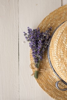 Auf dem strohhut liegt ein duftender lavendelstrauß. draufsicht