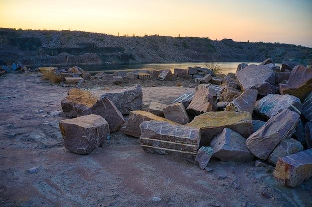 Auf dem territorium des alten überfluteten steinbruchs liegen große felsbrocken im warmen abendlicht.
