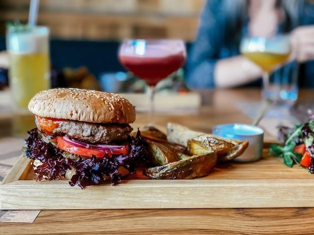 Auf dem tisch des restaurants ein burger mit kalbsschnitzel ein ring aus rotem zwiebel-basilikum eine tomate an