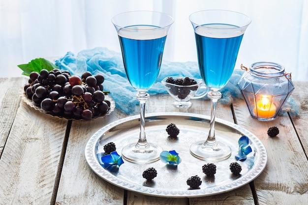 Auf dem tisch ein blaues getränk in transparenten gläsern, trauben und eine kerze in einem blauen kerzenständer