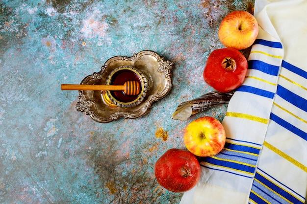 Auf dem tisch in der synagoge stehen die symbole von rosch haschana-apfel und granatapfel, schofar-talith