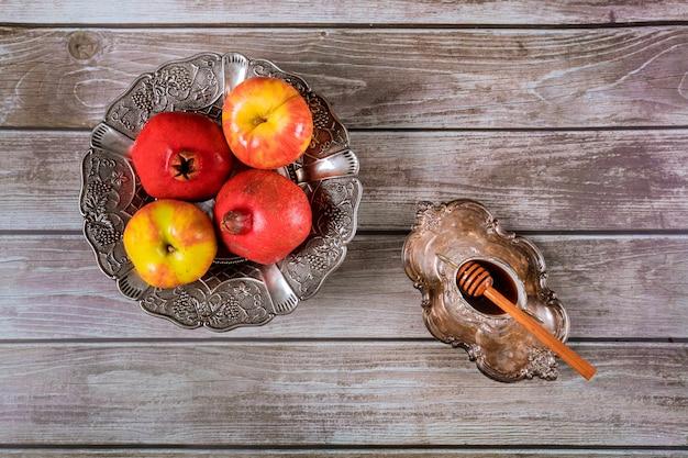 Auf dem tisch in der synagoge stehen die symbole von rosch haschana-apfel und granatapfel