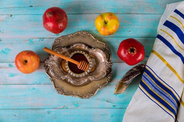 Auf dem tisch in der synagoge stehen die symbole von yom kippur apfel und granatapfel, shofar talith
