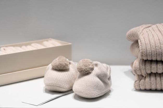 Auf dem tisch liegen babyschuhe, pullover und socken aus beigen naturstoffen.