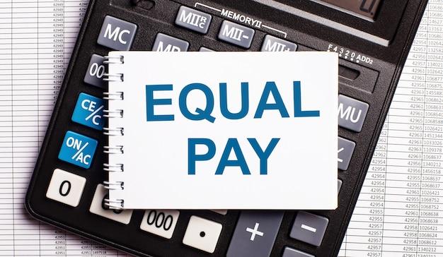 Auf dem tisch liegen berichte, ein taschenrechner und eine karte mit den worten equal pay. unternehmenskonzept
