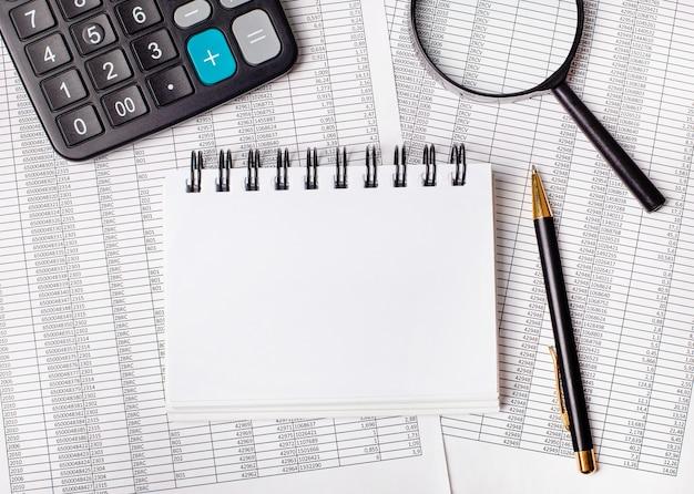 Auf dem tisch liegen berichte, eine lupe, ein taschenrechner, ein stift und ein weißes notizbuch mit platz zum einfügen von text oder abbildungen. vorlage. geschäftskonzept