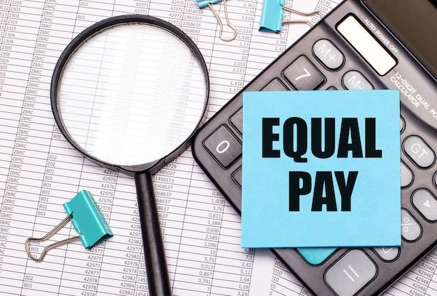 Auf dem tisch liegen berichte, eine lupe, ein taschenrechner und ein blauer notizaufkleber mit den worten equal pay. unternehmenskonzept