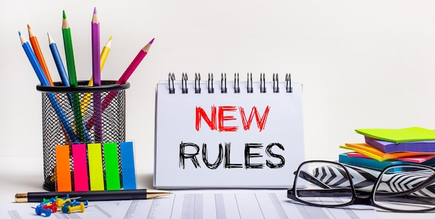 Auf dem tisch liegen buntstifte in einem ständer, bunte aufkleber, gläser und ein notizbuch mit der aufschrift neue regeln. motivierendes konzept. aufruf zum handeln