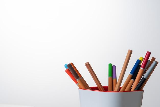 Auf dem tisch liegen buntstifte, zeichenblätter mit grafiken.