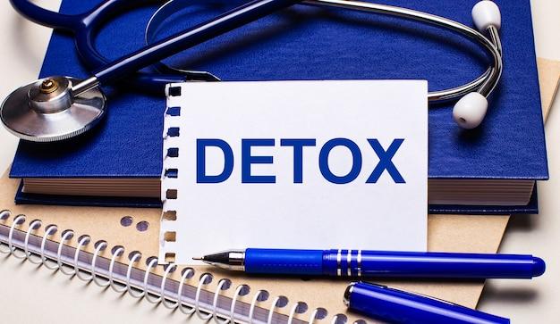 Auf dem tisch liegen notizblöcke, ein stethoskop, ein stift und ein blatt papier mit den texten detox. medizinisches konzept