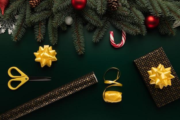 Auf dem tisch liegen papier und andere vorräte zum verpacken von weihnachtsgeschenken